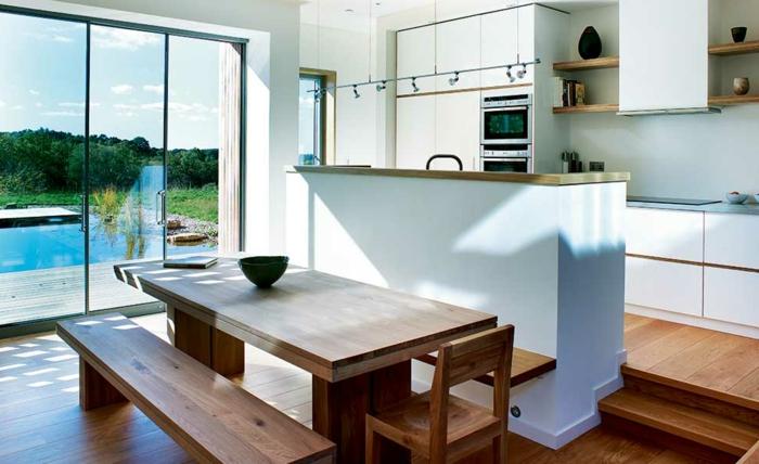 offene-küche-mit-theke-holzboden-treppen-esstisch-holz-sitzbank-holz-holzstuhl-weiße-küchenfronten-schwimmbadaussicht