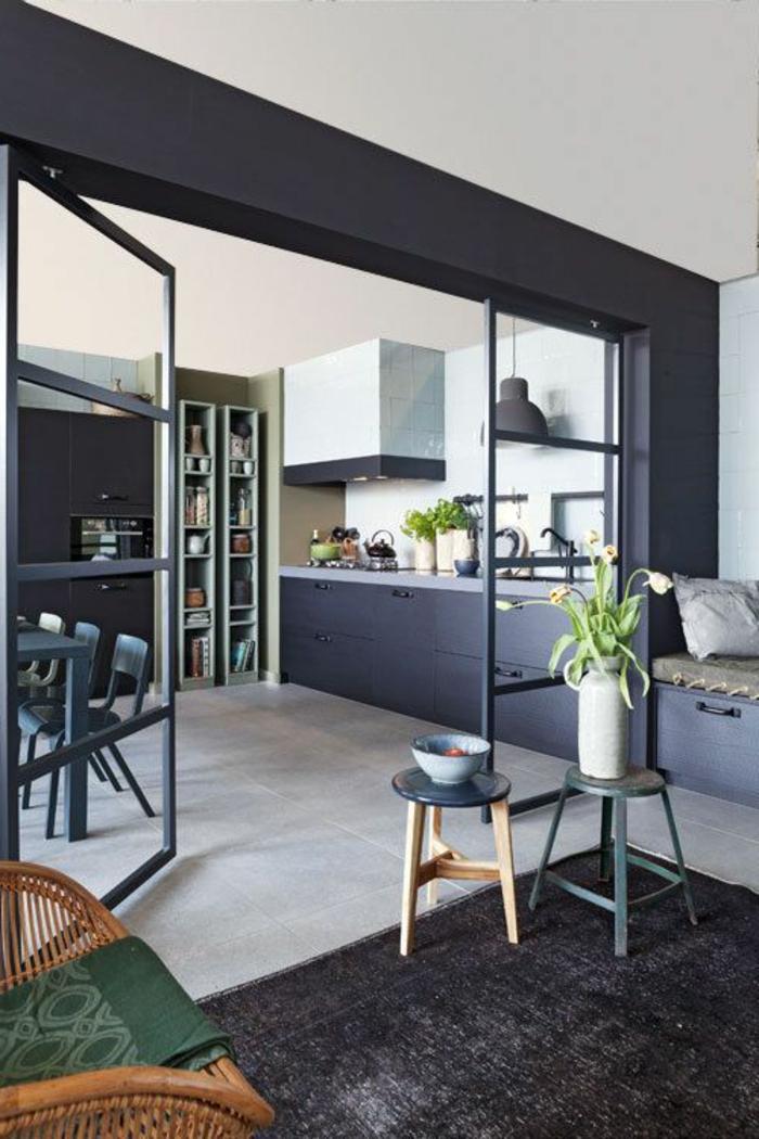 offene-küche-trennen-glastür-küchenregale-schwarze-küchenfronten-esstisch-holz-grün-schwarzer-teppich-flechtstuhl-holzhocker-bett