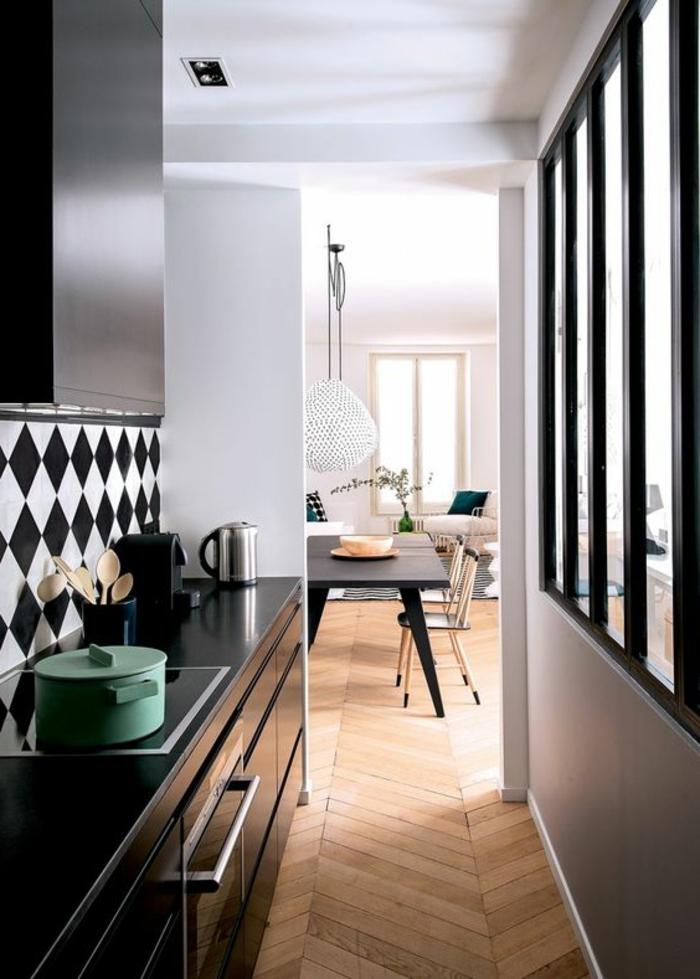 offene-küche-trennen-schwarze-küchenfronten-glas-raumteiler-parkett-grüne-topf-holzlöffel-set-kocher-esszimmertisch-schwarz-holzstühle-sessel-weiß-musterteppich-pflanze