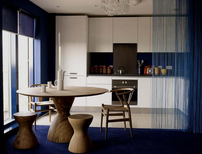 offene-küche-wohnzimmer-abtrennen-runder-esstisch-massivholz-holzstühle-blauer-plüschteppich-rollos