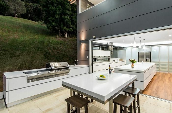 eine sehr moderne Außenküche mit Waldaussicht