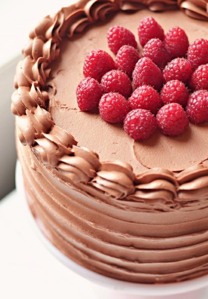 red-velvet-cake-getoppt-mit-schoko-sahne-creme-deko-spritz-und-himbeere-darauf-gestellt-roter-samtkuchen