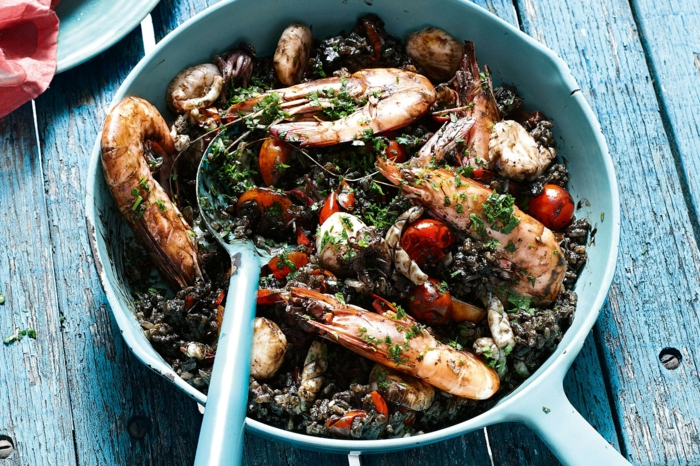 schwarzer reis rezept mediteranes essen garnellen tomaten basilikum blaue farbe holztisch