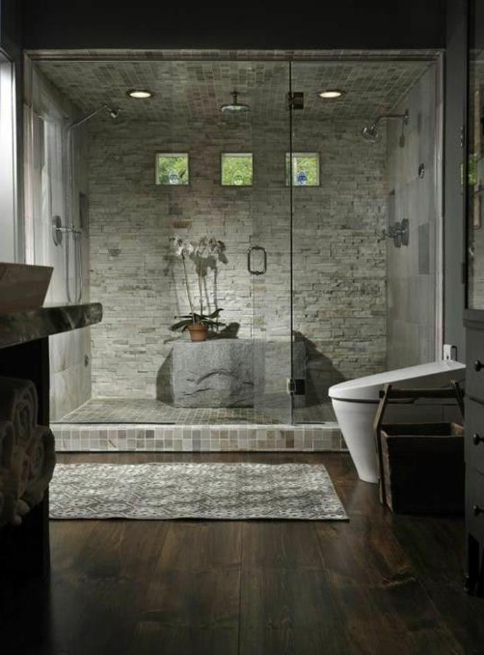 badezimmer mit naturstein und holz und duschkabinne