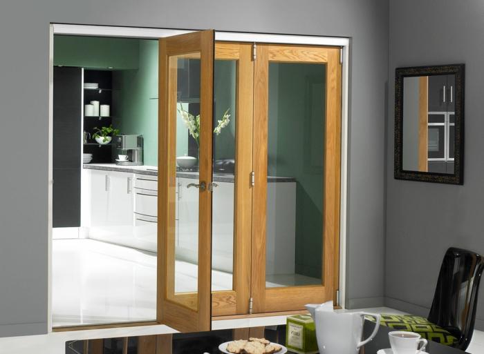 schiebetür-küche-harmonikatür-glas-holz-grüne-wand-schwarzer-esstisch-spiegel-schwarzer-plastikstuhl