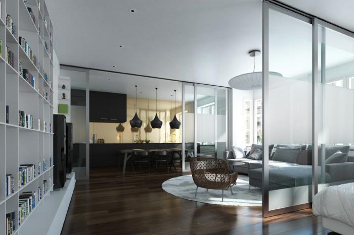 schiebetür-küche-industril-wohnzimmer-graue-eckcouch-flechtstuhl-weißer-runder-teppich-bücherregal-bett