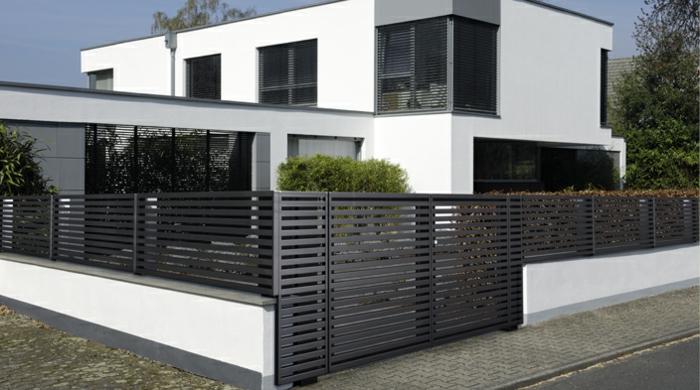 modernes Haus in Schwarz und Weiß mit Gartenzaun aus Metall