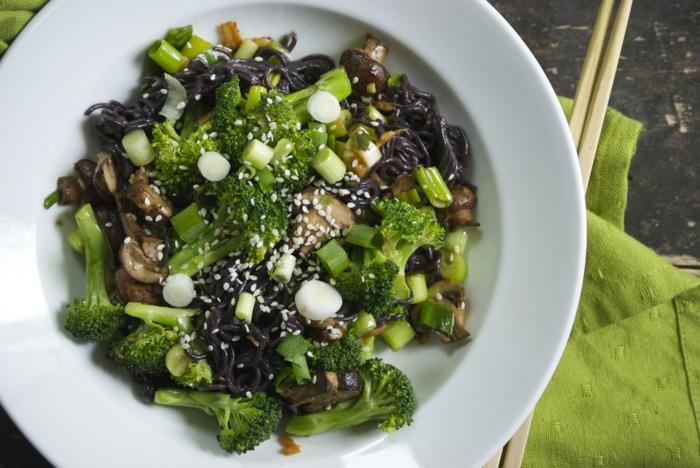 schwarzen reis kochen grüne teller gestalten speise mit brokkoli zwiebeln mit stäbchen essen