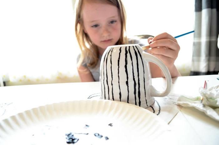 tassen-bemalen-mit-kindern-ein-süßes-blondes-mädchen-malt-schwarze-linien