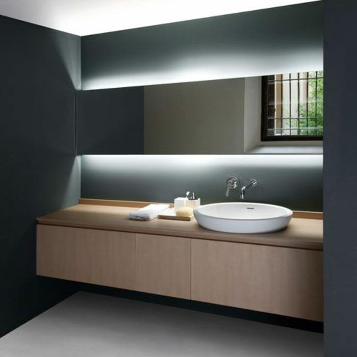 badezimmer in grau mit weißem waschbecken mit unterschrank und großem spiegel