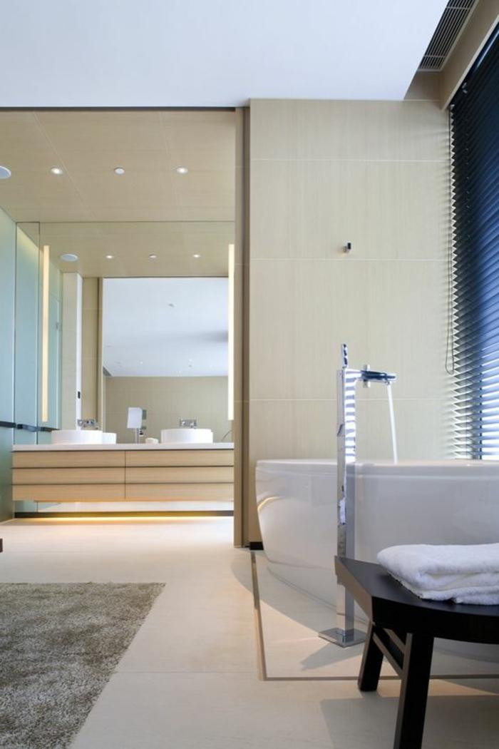 elegantes badezimmer in hellbraun mit weißer badewanne