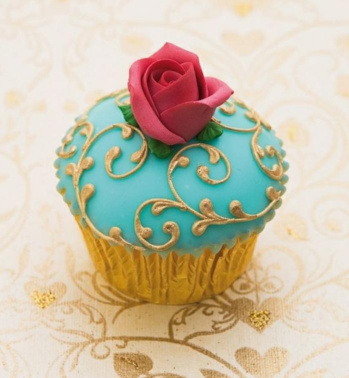 muffin mit blauem fondant mit goldenen elementen und roter rose