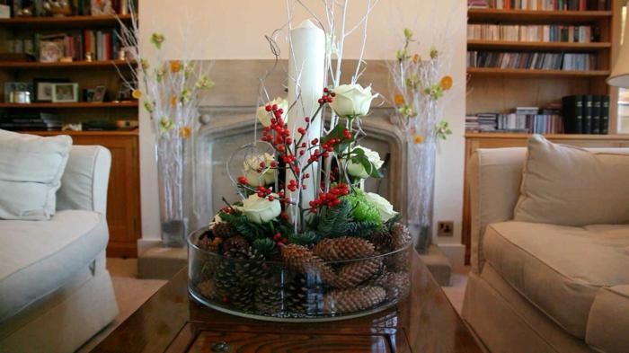 eine saisonale Deko mit Zapfen, weißen Rosen, roten Beeren und einer großen weißen Kerze