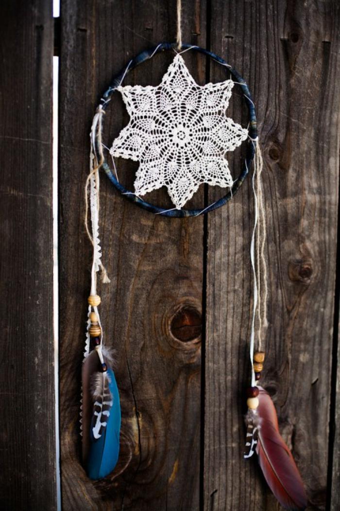 blauer Traumfänger mit dünnen Lederriemen und bunten Federn