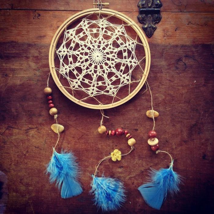 Traumfänger aus Holz mit weißer Broderie, blauen Federn und roten Holzperlen