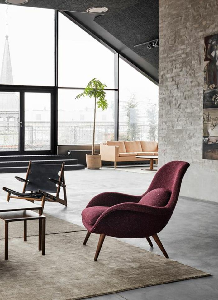 minimalistisches Wohnzimmer mit Ziegelwand, hellpinker Couch, weinrotem Polsterstuhl und indirektem Licht