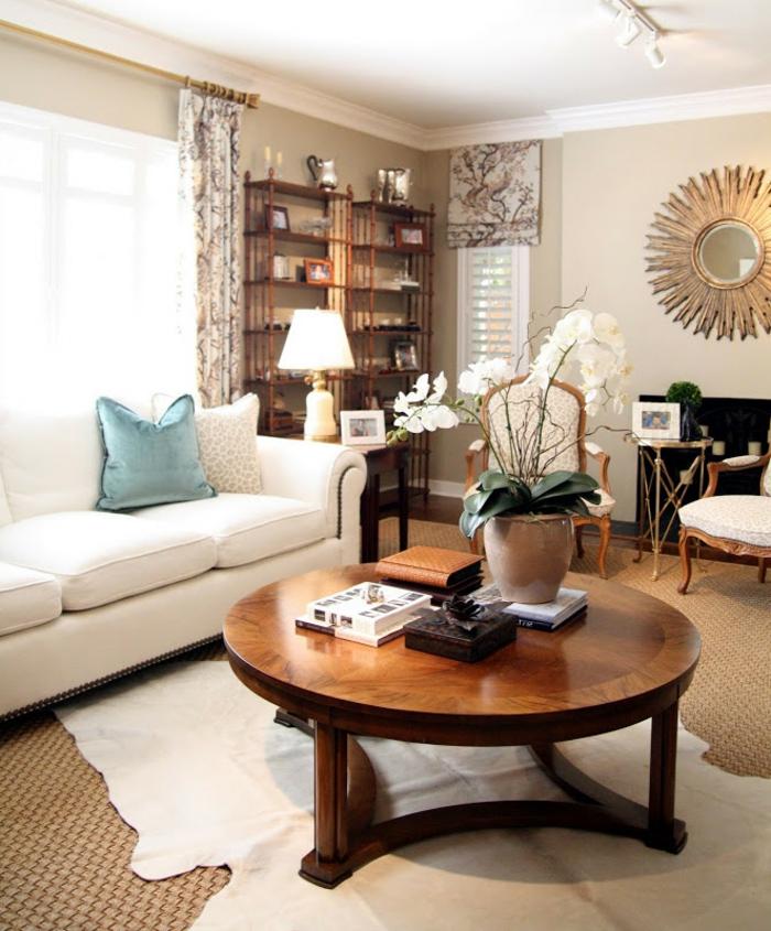 Wohnzimmer Deko Ideen: ein runder Couchtisch aus Holz mit einer weißen Orchidee zur Dekoration