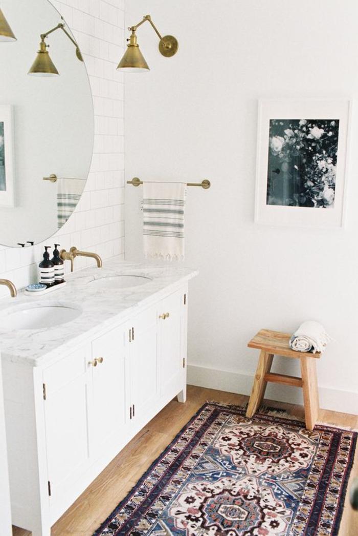 minimalistisches Badezimmer mit rundem Spiegel mit einfachem Rahmen, kleiner Holzstuhl, Musterteppich