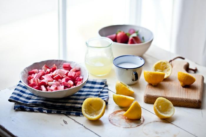 Rhabarber in weißer Schüssel, Erbeeren, Zitronensaft in einer Glaskane, Zitronenschalen