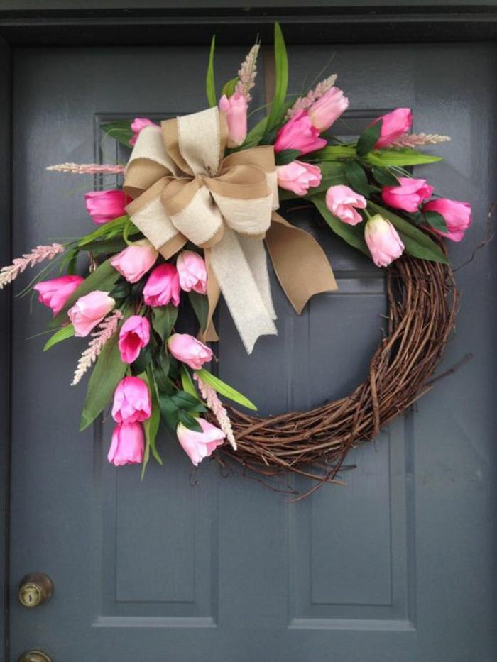 frühlingsdeko basteln, graue tür. türdeko, kranz aus zweige dekoriert mit tulpen und beige schleife aus leinen