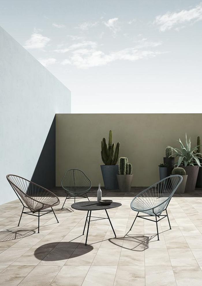 Dachterrasse im minimalistischen Stil mit drei Metallstühlen und einem schwarzen Kaffeetisch, riesengroße Kakteen