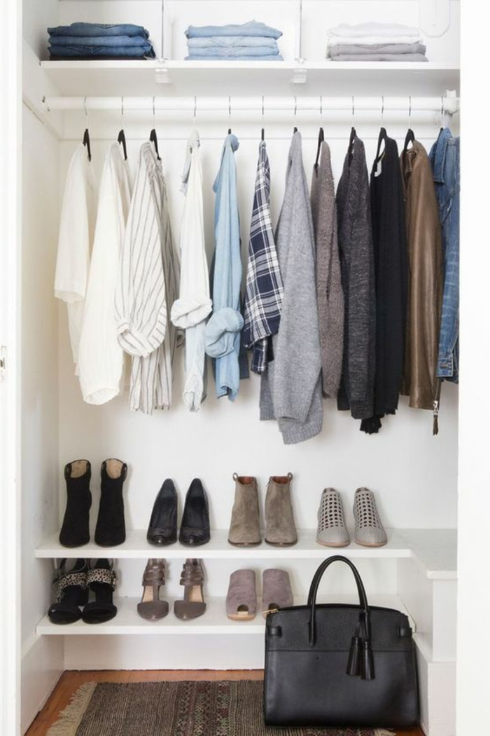 weiße Garderobe mit einem Regal mit gefalteten Jeans, Hemden und Pullis, Schuhe, Teppich, Ledertsche in Schwarz