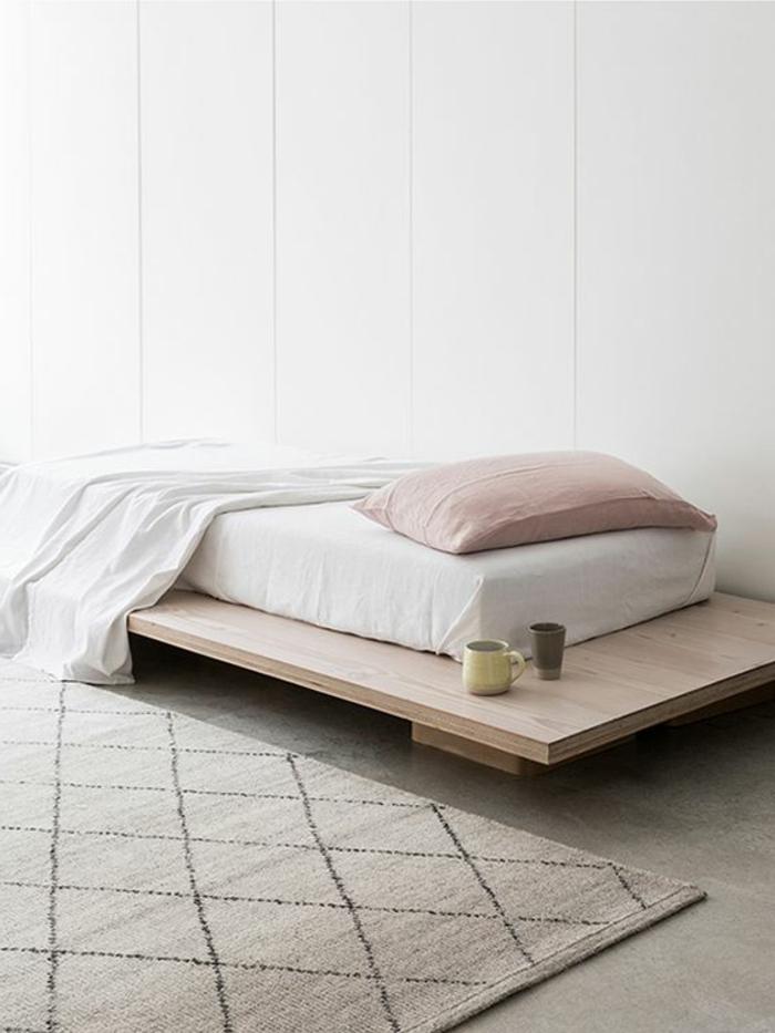 Schlafzimmer mit Einzelbett, weiße Bettwäsche, aschenrosa Kissen, zwei Kaffeetassen, Musterteppich