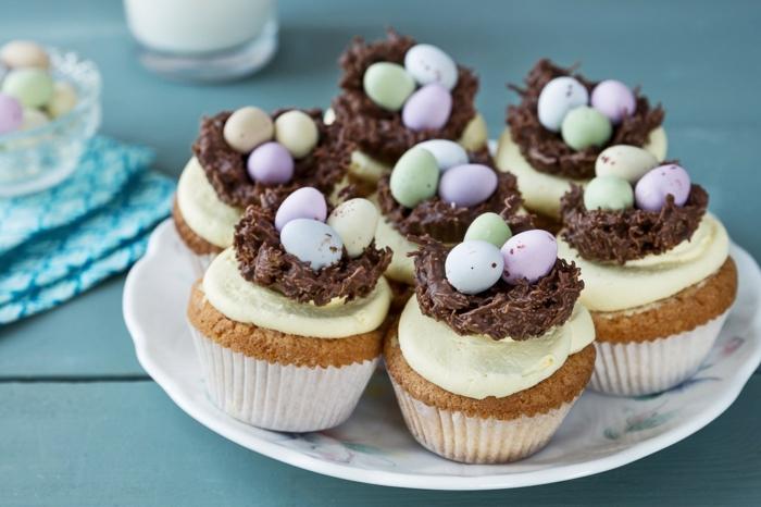 Oster Cupcakes mit gelber Glasur und bunte Eier in Nest aus Schokolade