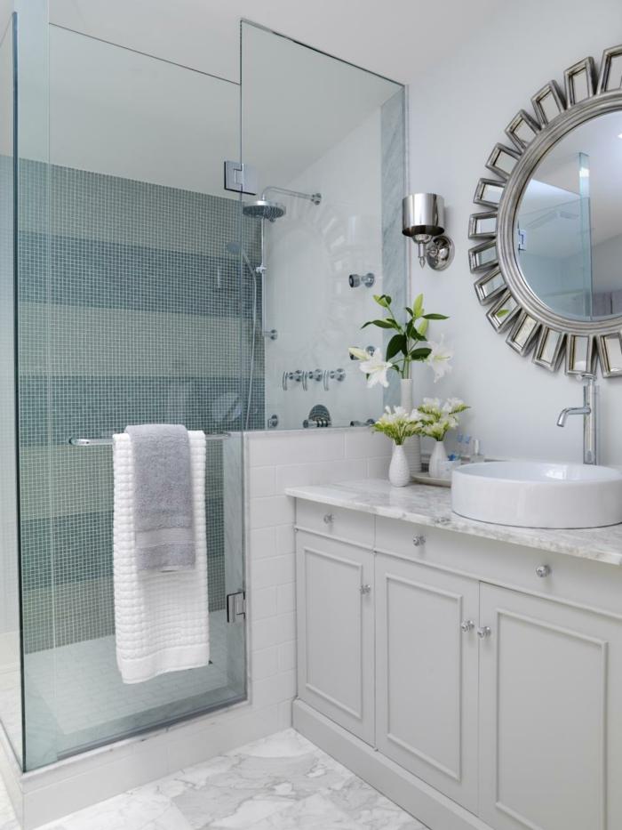 runder Spiegel wie Sonne weiße bemusterte Bodenfliesen und Mosaikfliesen an der Wand der Duschkabine- moderne Badfliesen