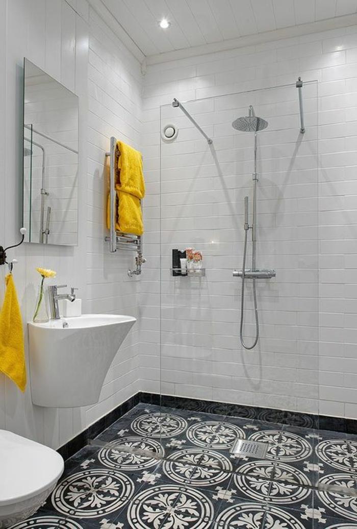 Glaswand als Raumteiler, gelbe Tücher, schwarze bemusterte Kacheln - moderne Badfliesen