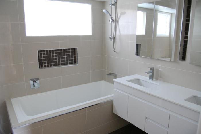 beige moderne Badfliesen, eine Nische Spiegeltüren des Regals, moderne Badewanne