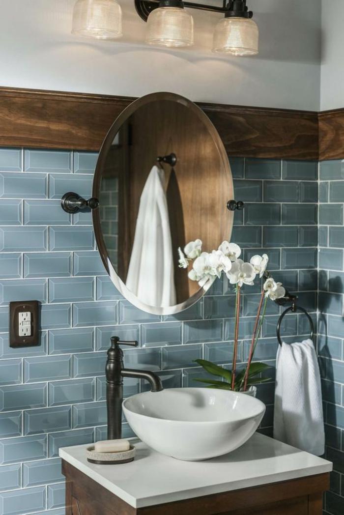 Fliesengestaltung Bad - blaue Wandfliesen, runder Spiegel, weiße Blumen als Dekoration