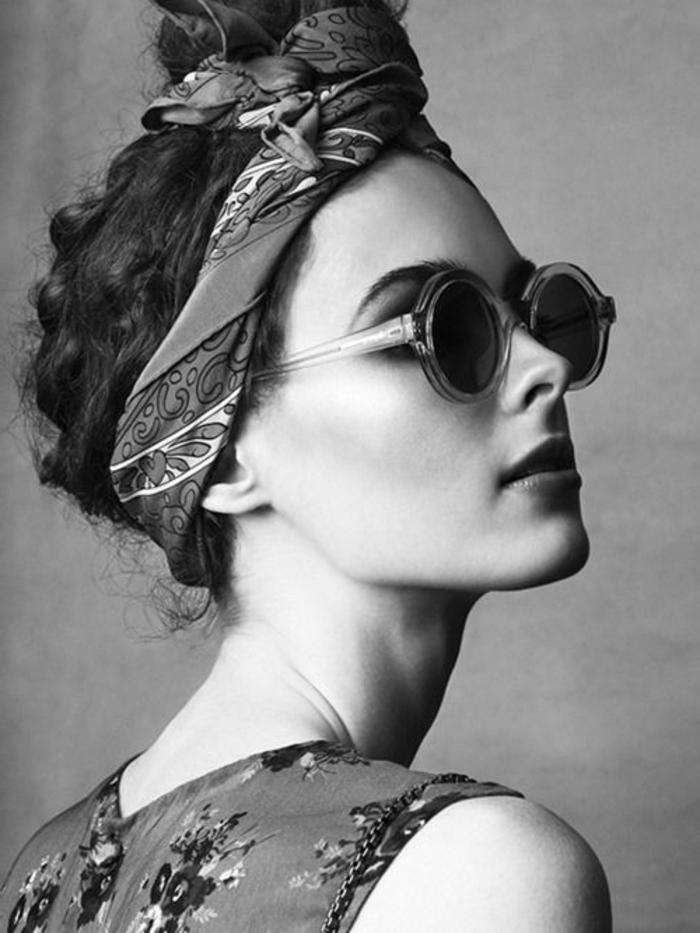 frau mit hochsteckfrisur mit bandana, kleid mit blumen und runden sonnenbrillen