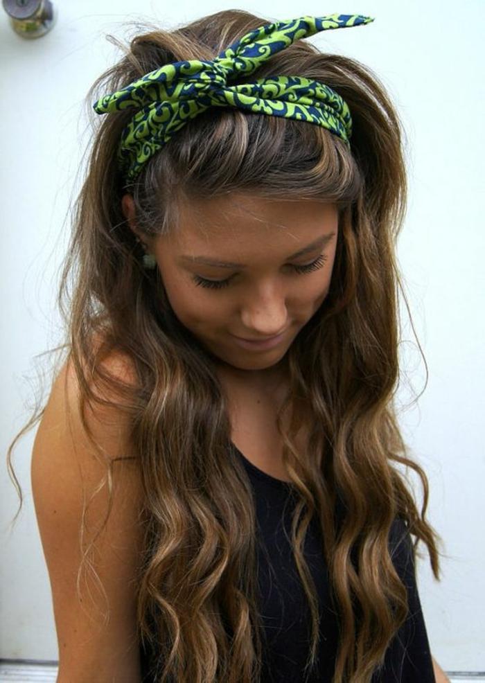 dame mit langen, lockigen, braunen haaren und blauem bandana mit grünem muster
