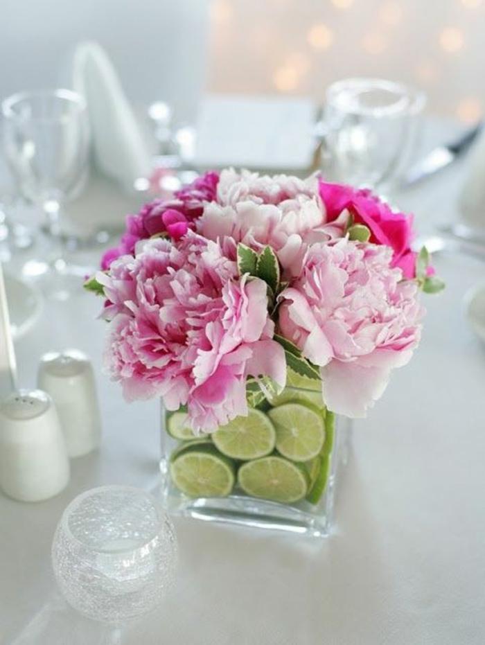 eckige glasvase dekoriert mit limettenschalen, rosa blumen, tischdeko