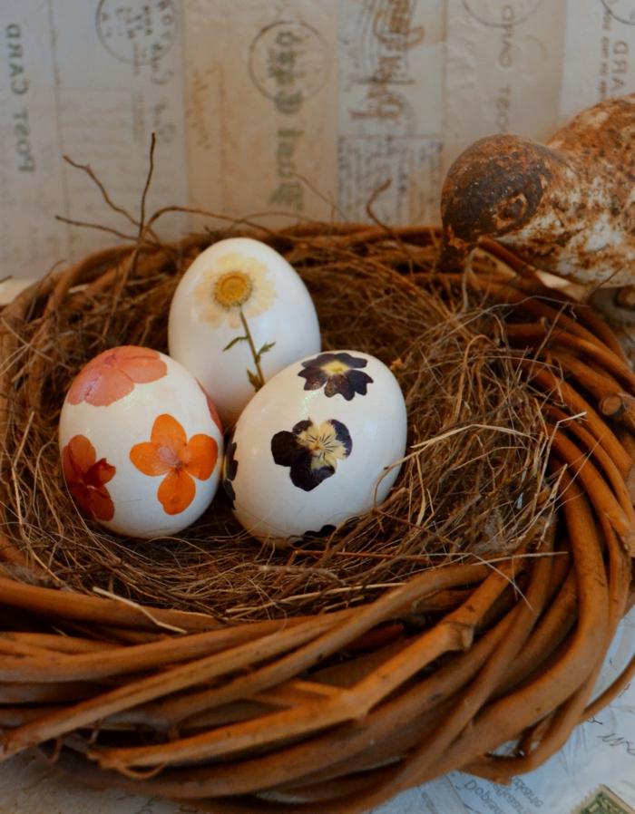Lustige Ostereier mit verschiedene Blumen bemalt und im Nest gestellt