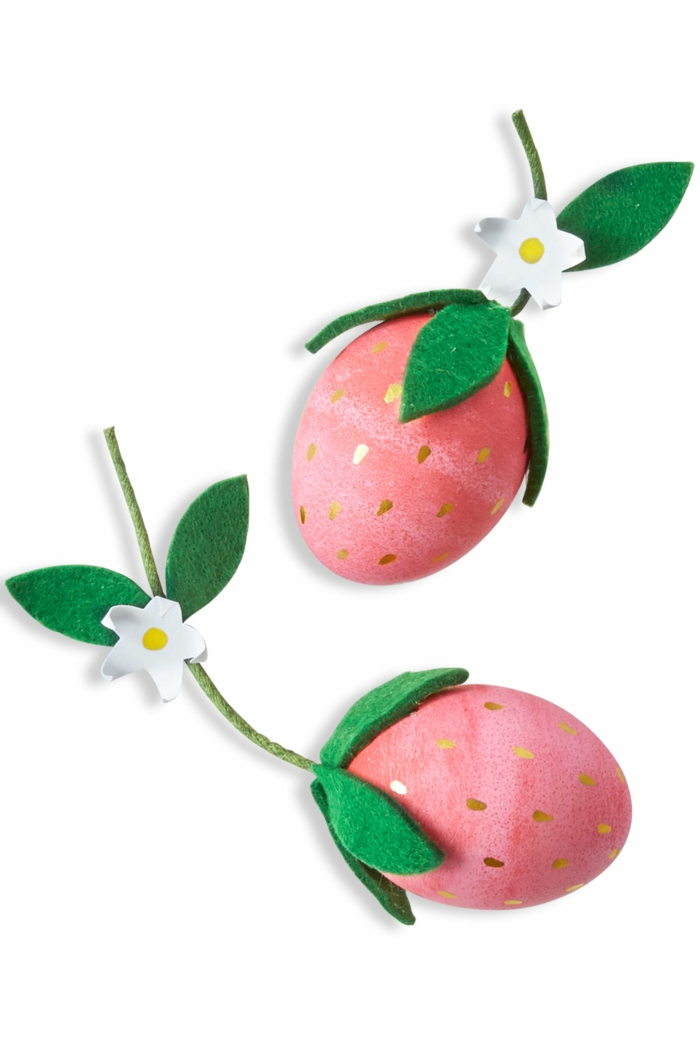 rote lustige Eier mit Tropfen, um wie Erdbeeren zu aussehen mit einen weißen Blüten