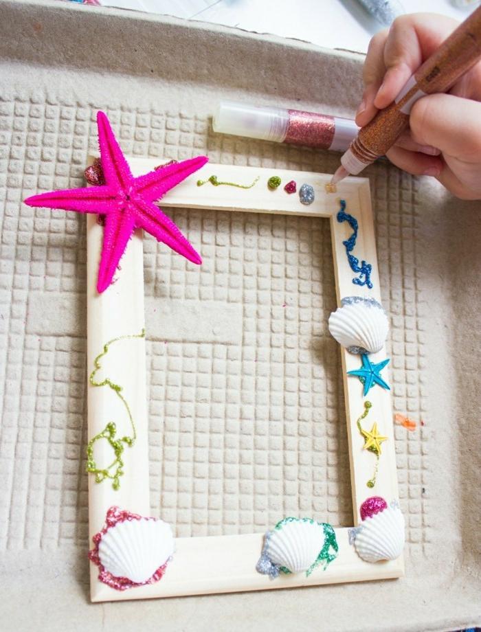 weißer rahmen dekoriert mit muscheln, rosa stern und brokat