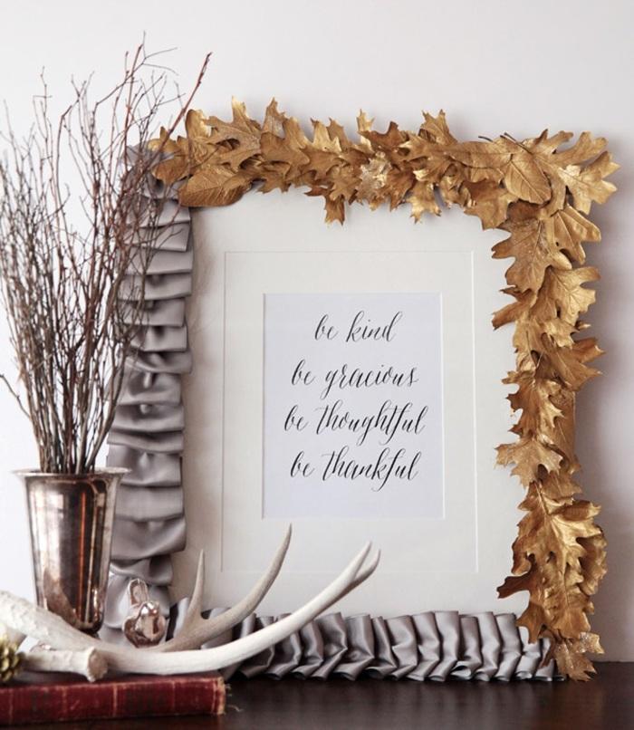selbstgemachteter fotorahmen dekoriert mit grauer schleife und goldenen baumblättern