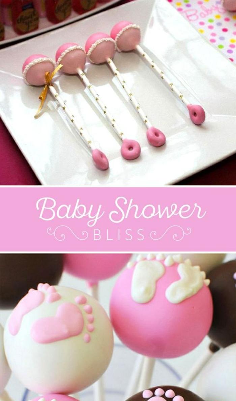 cake pops dekoriert mit rosa und weißer glasur wie kleine babyrasseln