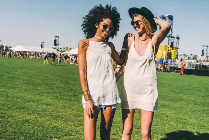hippie festival outfits zwei schöne frauen haben spaß auf dem grünen feld musik hören und genießen