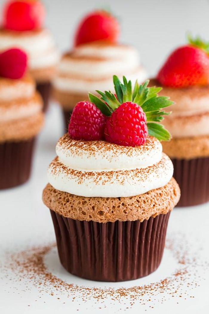 schoko-cupcake mit weißer sahne, himbeeren und zimt dekorieren