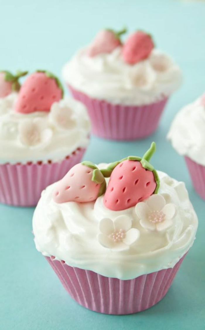 muffins mit weißer sahne, kleine blümchen und erdbeeren aus fondant