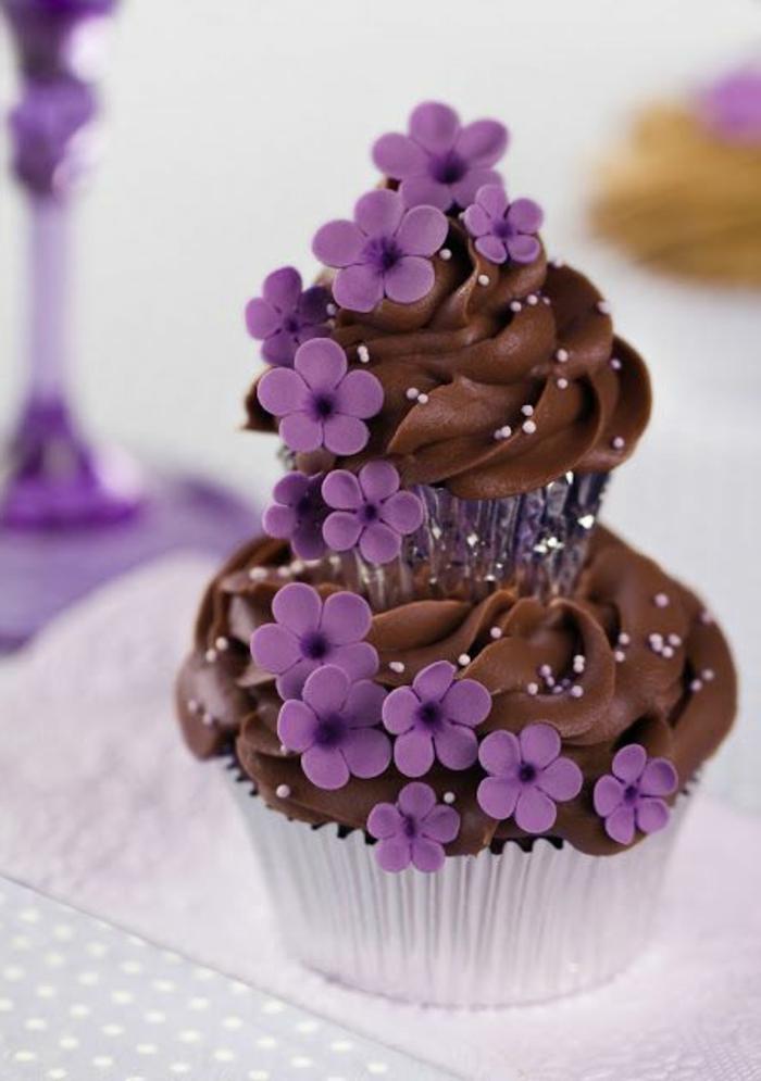schoko-cupcake mit sahne und lila blümchen verzieren