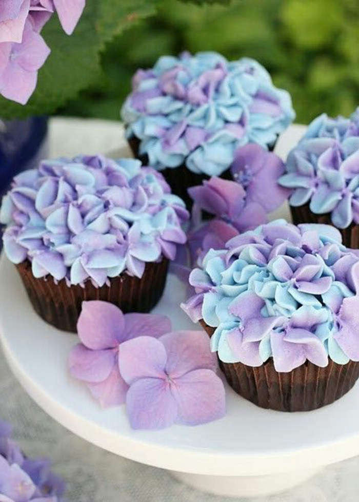 muffins mit blumen aus sahne in blau und lila dekorieren