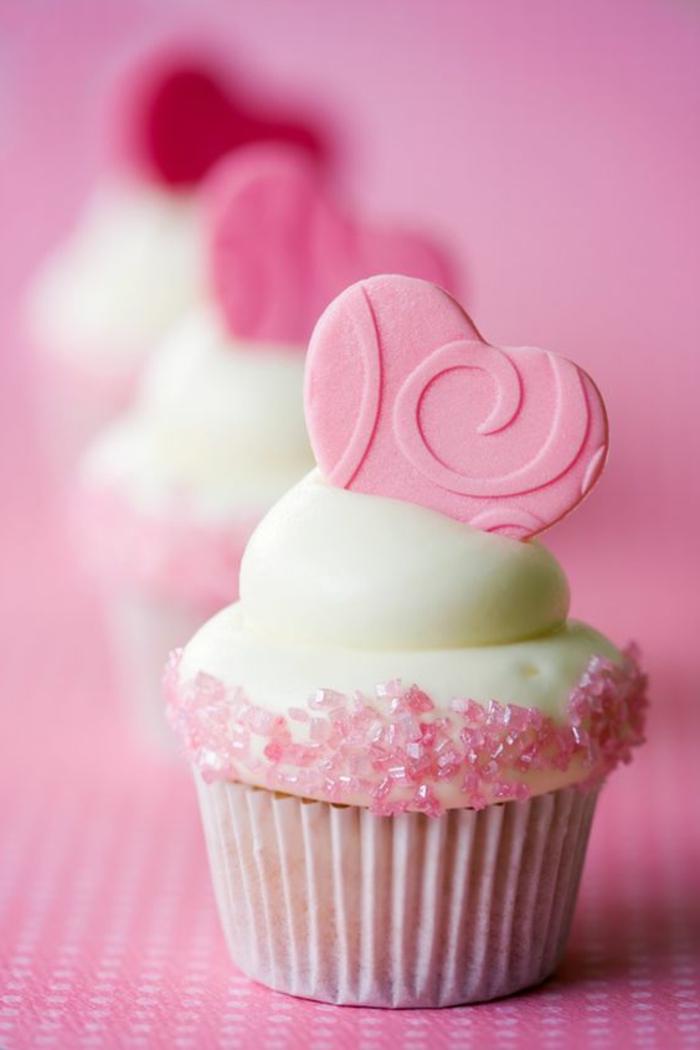 süßer supsake mit weißer sahne und herz und rosa fondant