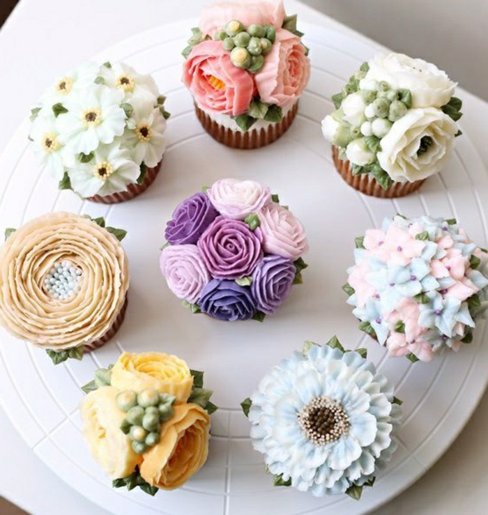 muffins dekoriert mit verschiedenen blumen aus sahne