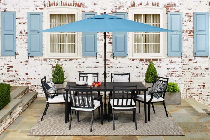terrassengestaltung ideen großer tisch mit sessel stühle kissen blauer schirm fenster türen