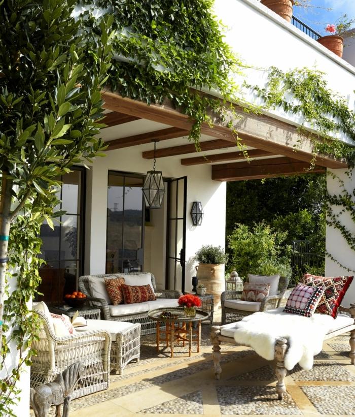 terrassengestaltung ideen gemütliche terrasse sofa sessel pelz teppich kissen blumen deko pflanze