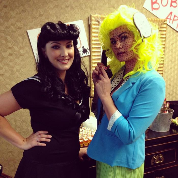 zwei Mädchen mit vintage Kostüme und Frisuren, vintage Kleider und das eine hat Hörer